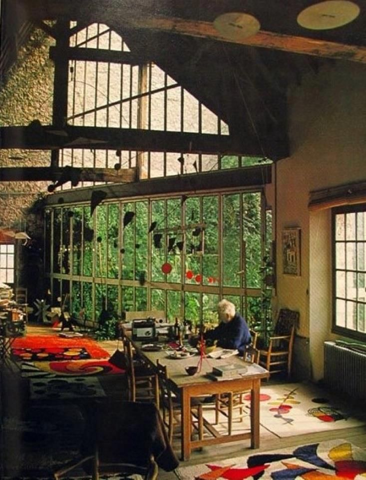 Big windows, surrounded by lush trees on a hillside, cozy, surrounded by artistic materials, free to create all day