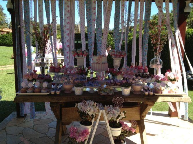 """A mesa montada pela equipe da Scrap Fest (scrapfestvs.blogspot.com.br) tinha """"cupcakes"""", biscoitos decorados, maçãs cobertas com chocolate, """"cakepops"""" (bolos no palito), doce de leite no copinho, bombons e brigadeiros. Tiras de tecidos com estampas florais formavam um painel atrás da mesa. No chão, a decoração dessa festa com tema primaveril ficou por conta das azaleias, dispostas em suportes de ferro"""