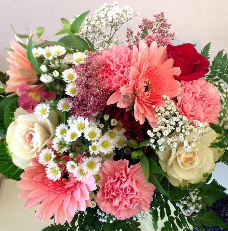 Coral and cream cluster of flowers. Including decorative cabbage, gerberas, babies breath, carnations and rice flower.