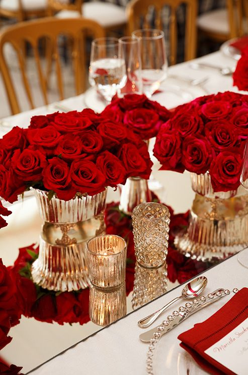 Gorgeous mirrored table runners reflect fresh red roses in opulent gold containers.