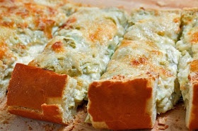 1 (14 ounce) can artichoke hearts, drained and chopped   2 green onions, sliced   2 cloves garlic, chopped   4 ounces cream cheese, room temperature   1/4 cup mayonnaise   1/2 cup sour cream   1/2 cup mozzarella, shredded   1/4 cup parmigiano reggiano (parmesan), grated   1 loaf Italian bread, sliced in half lengthwise