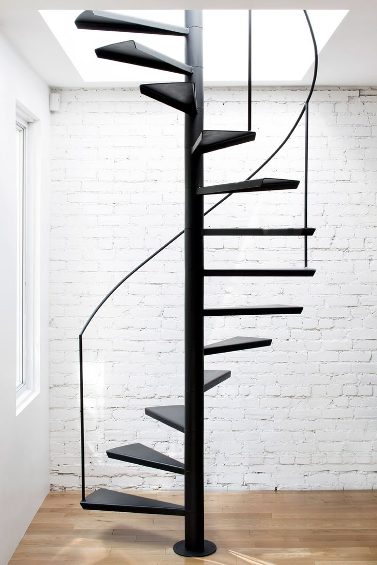 A blackened-steel staircase, which was welded and assembled on site, allows access to a wood-decked roof terrace of a Montreal apartment.