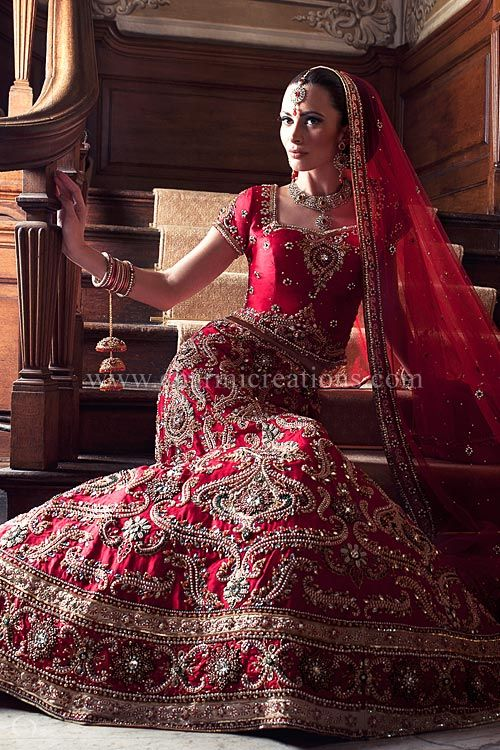 Red raw silk Asian wedding lehenga with pearls and zardosi work with highlights of emerald green stones