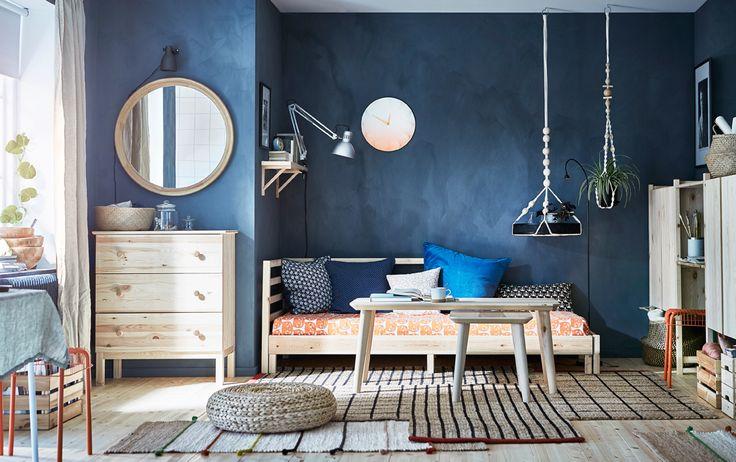 Estudio moderno de estilo escandinavo con paredes de color azul oscuro y un diván/sofá cama de pino.