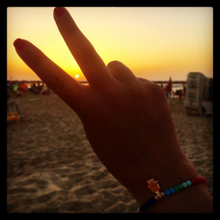 Hands up to a magnificent sunset with our #danalevy mini hamsa hand charm rainbow glass bead bracelet.