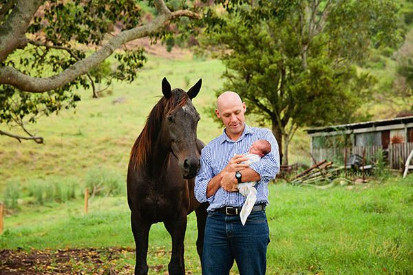 proud dad introduces newborn son to his horse on his country property.
