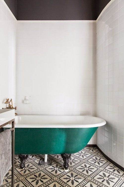 Bathtub of emerald color with beautiful black and white tiles, a stunning contrast.