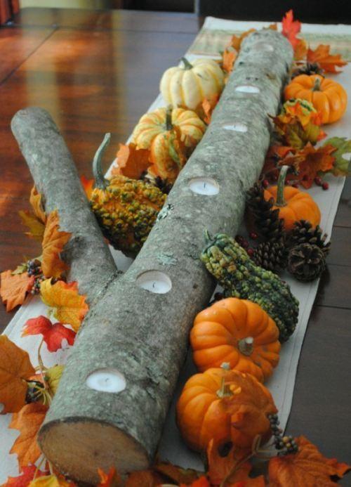 A log with tea lights, decorative leaves and mini pumpkins.