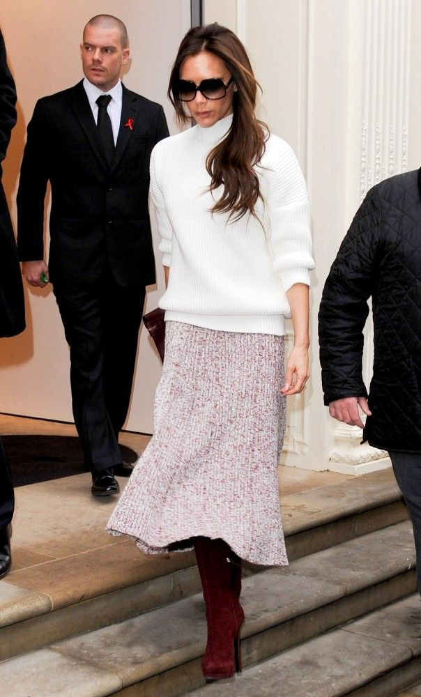 Victoria Beckham kept warm in a cozy ivory turtleneck, pale pink plated midi skirt and suede boots