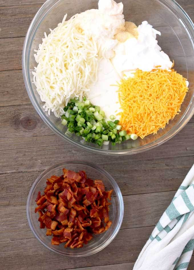 View of ingredients to make this bacon dip. In a big glass bowl, cream cheese, sour cream, mayonnaise, shredded mozarella, shredded cheddar, garlic powder and sliced green onions on a wooden surface.