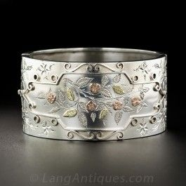 Hailing from Birmingham, England circa 1883 (according to the hallmarks), a 1 1/4 Inch wide and wonderful Victorian bangle bracelet rendered in silver and overlaid with a charming floral and engraved foliate design rendered in contrasting two-tone rose and yellow gold, and enclosed by a raised geometric and scrolled border. Lovely.