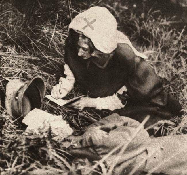 Ošetřovatelka Červeného kříže zapisuje poslední slova umírajícího vojáka (1917)