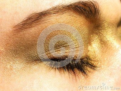 A close-up view of a teenage girls closed eye made up with glittering green, gold and bronze eye shadow.