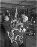 Vervaardiger: Ary Groeneveld | In een brandweerkazerne zijn twee geuniformeerde brandweerlieden bezig een kerstboom op te tuigen; de motorbrandspuit Ahrens Fox op de achtergrond.| Datering: 20/11/1968-20/12/1968 (Geschat)   | Klik op Bezoeken om de grote versie te bekijken. | Catnr. NL-RtSA_ 4121_11304