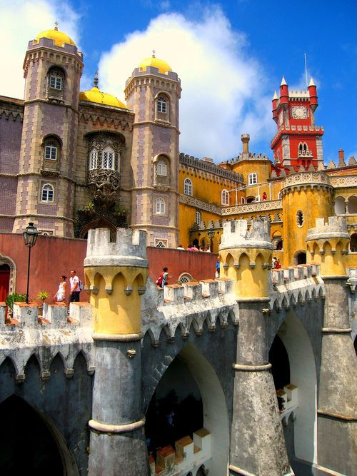 Pena National Palace in Sintra, Portugal. With its multicolored exterior walls and its eclectic aesthetic styles, Portugal's Palácio da Pena almost resembles a cake covered with colorful frosting. The romantic, fanciful castle was built on a craggy hill near Lisbon in the first half of the 19th century and incorporates elements of German, Moorish and other architectural traditions.