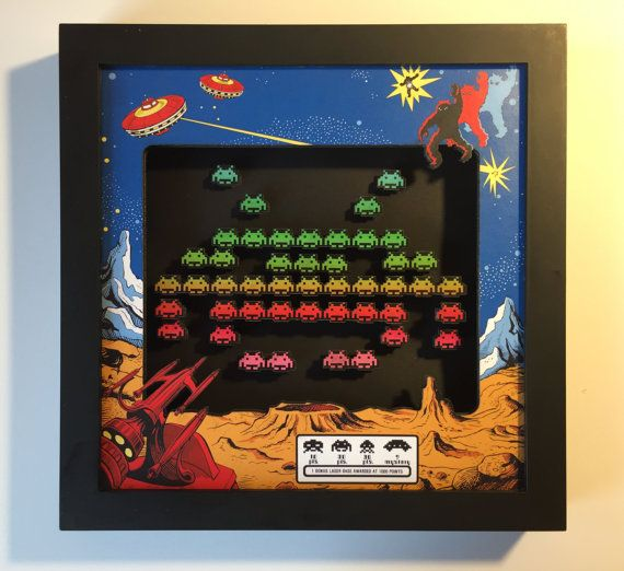 Its a Space Invaders shadow box! The art is made from meticulously cut prints and foamboard, and shows invading hordes of aliens, descending in the