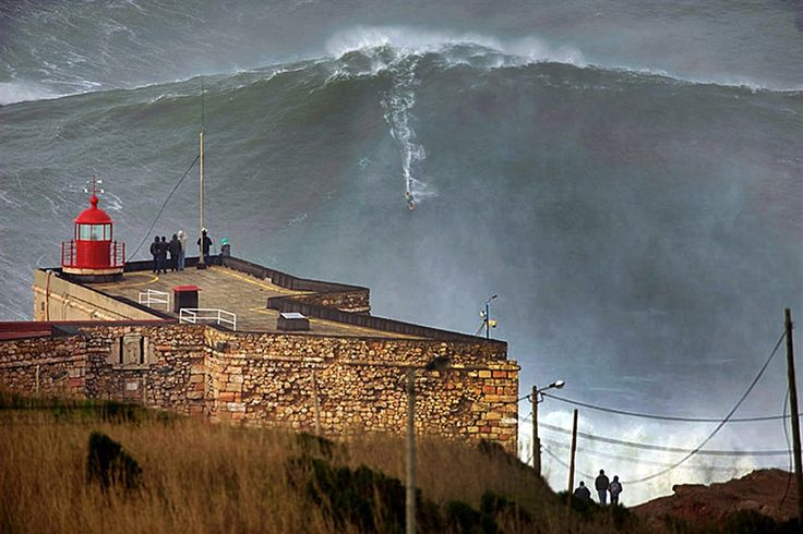 Surfer Garrett McNamara catches what could be the largest wave ever surfed, off the coast of Nazare, Portugal, on Jan. 29. The estimated 100-foot wave, if confirmed, would beat the current world record of 78 feet, which McNamara has held since 2011.
