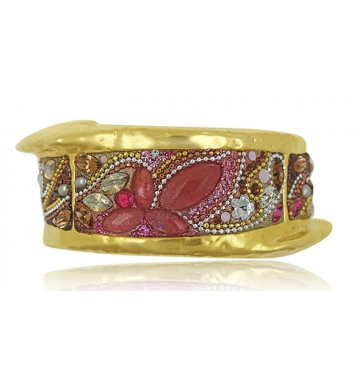 A chunky gold-plated piece capturing the sweeping season of autumn with its Swarovski coloured crystals resembling leaves in the shades of orange, yellow, pink and red, ones that surpass the beauty of those evergreen. This piece's form twists and turns like the wind that carries these multi-coloured treasures from branch to floor. It's the kind of piece that adds a touch of shine and warmth to any outfit worn.