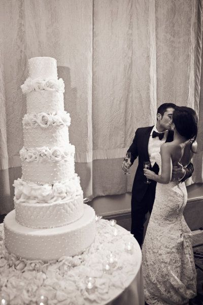 .lovely wedding and cake towered with flowers between kiss in the middle bride and groom black and white