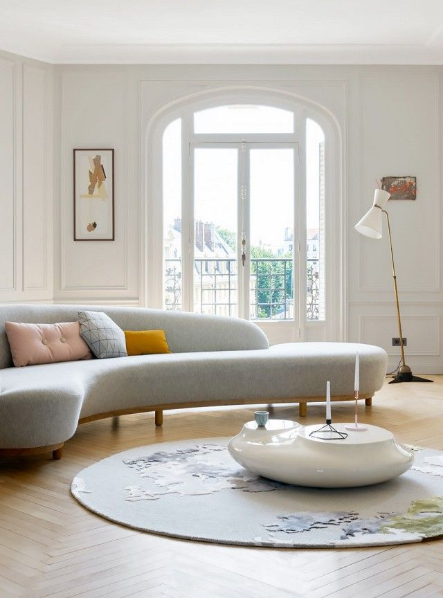 Parisian-chic living space with a curved sofa, and herringbone wood floors