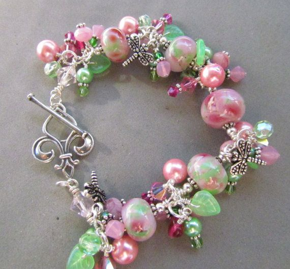 In the Rose Garden Just in time for Valentines Day or Mothers Day. Perfect for gift giving or as a gift for yourself! Handmade beaded lampwork bracelet in pinks and green accented with swarovski crystals, czech glass beads, bali silver and dragonfly charms. Handmade by me here in my Florida studio. All the lampwork beads were lovingly made using Moretti and CIM glass and are kiln annealed for strength and durability. Large Sterling silver toggle closure. Materials: Handcrafted glass lam...