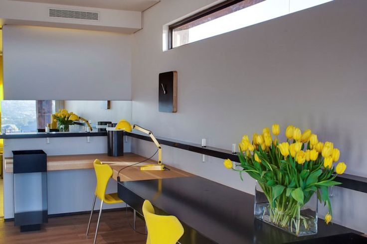 A thin window above the large corner desk, along with yellow chairs and accents, brightens up this home office for two.