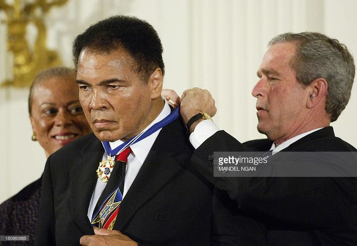 US President George W. Bush (R) presents the Presidential Medal of Freedom, the nation's highest civil award,to boxer Muhammad Ali in the East Room of the White House 09 November 2005 in Washington, DC. The medal is presented to those who have made contributions to national security, world peace, or culture.It was Ali's first public appearance in five months. The last was also in Washington when he watched his daughter Leila Ali fight in a women's boxing bout. AFP PHOTO/Mandel NGAN