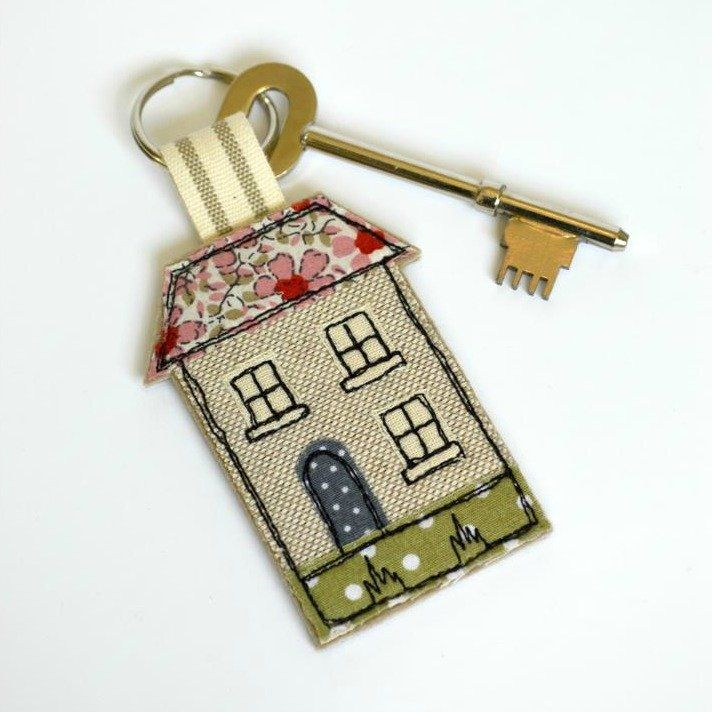 "Handmade New Home Card with a pretty fabric house shaped key-ring / key fob attached (pink floral roof).  The key ring is made from wool felt, cotton fabrics and ribbon.  Stitched using freehand machine embroidery.  Key-ring  Measures approx. 6.5cm x 5cm (2.5"" x 2"")  Split ring 22mm wide  Total length including ring and ribbon 10cm (4"")  The card is blank inside and comes with a matching envelope.  Card measures approx. 17.5cm x 12.5cm (7"" x 5"")  A card as well as a small gift for someone…"