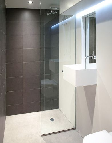 Beautifuly simple. Love the shower tile and curbless-shower entry, and wall-hung sink. white corian and concrete bathroom modern bathroom