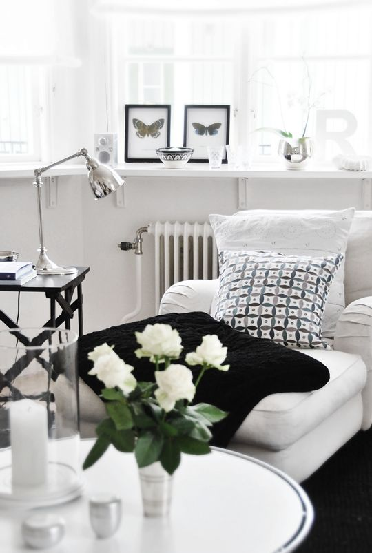 White interiors with black geometric pillow, frames, table and throw accents.