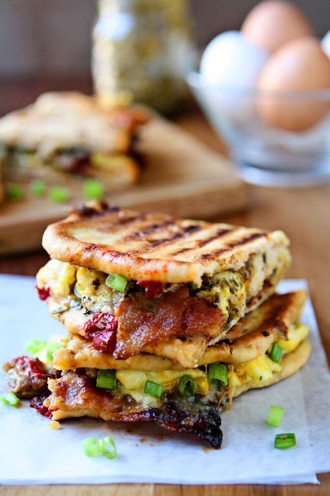 Breakfast Panini | Take your breakfast to the next level! Sun-Dried tomato pita bread, pesto, three kinds of cheese, scrambled eggs, bacon, sausage, roasted red peppers and scallions. A delicious and hearty breakfast sandwich that will keep you going all morning. Ready in less than 30 minutes!| heavenlyhomecooking.com