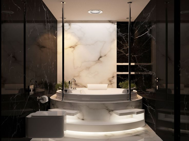 Luxury bathroom decor | A round marble bathtub illuminating the space was placed against a light colored marble wall and surrounded by black marble | #homedecorideas #marblebathrooms #luxurybathrooms