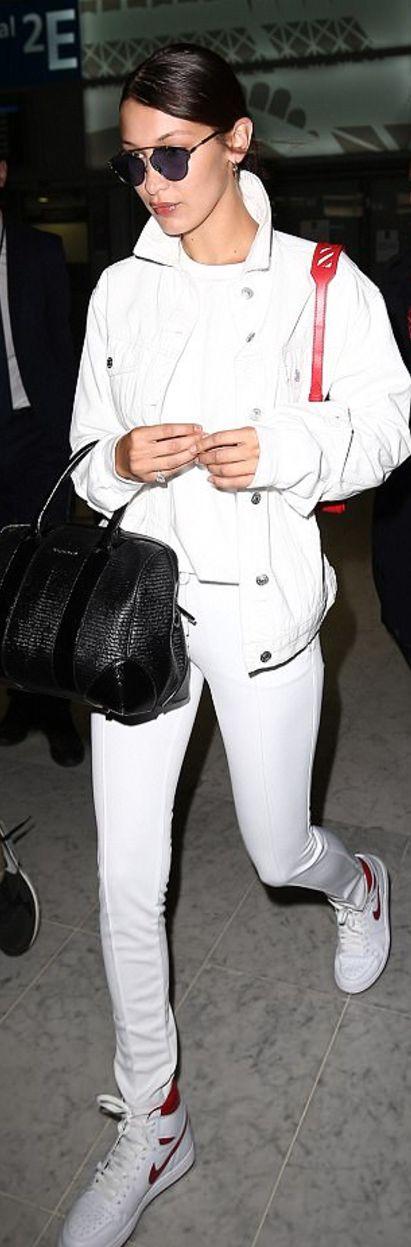 Who made  Bella Hadid's black sunglasses, handbag, pants, and white sneakers?