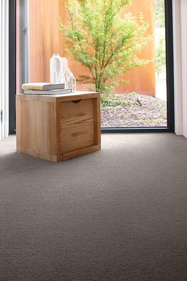 A plush pile carpet in a dark neutral hue highlights the natural beauty in light timber furniture.  Credits - Carpet: Godfrey Hirst Carpets; Timber box & ceramic vessel: Mark Tuckey.