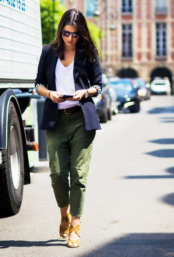 A white t-shirt is paired with a navy blazer, green pants, yellow sandals, and black sunglasses: