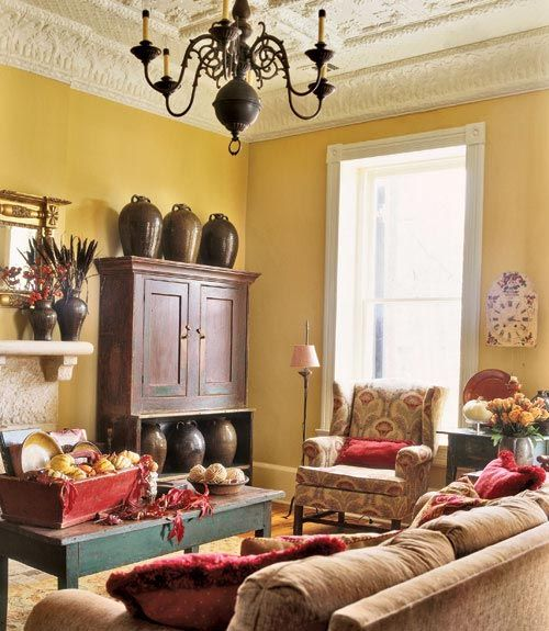 Visions of Fall: In the living room, a trio of five-gallon, double-handled syrup jugs commands attention atop an 1830s New England bucket cupboard. Here, a palette of soft gold, beige, and linen white is warmed with deep red accents—a checkerboard lampshade, fringe throw pillows, a faded wooden crate centerpiece—and complete an autumnal vision. Working within this color combination serves as an ideal backdrop antiques and treasured items.
