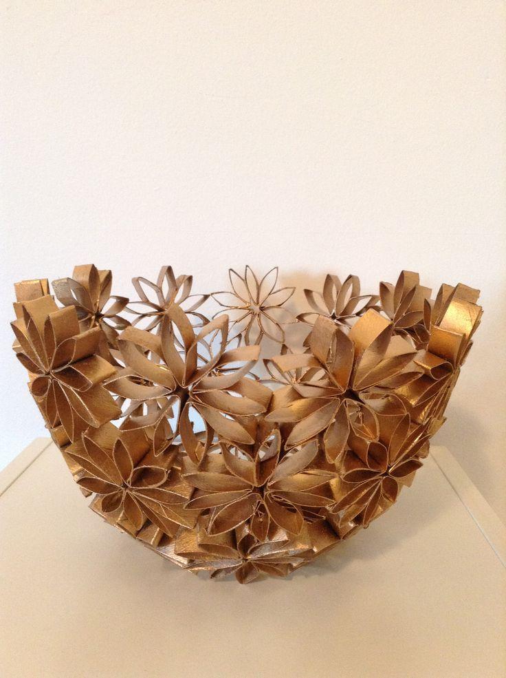 Materiales: • Bol de plástico. • Tubos de cartón. • Pegamento. • Tijera. Procedimiento: 1. Corta los tubos de cartón en trozos de 2 cm aproximadamente, luego realiza flores con 10 u 11 pétalos cada uno. 2. Cuando tengas las flores listas comenzaremos a realizar el recipiente de flores de cartón. 3. Utiliza el bol de plástico como base y comienza a unir las flores hasta lograr que este tenga la misma forma.