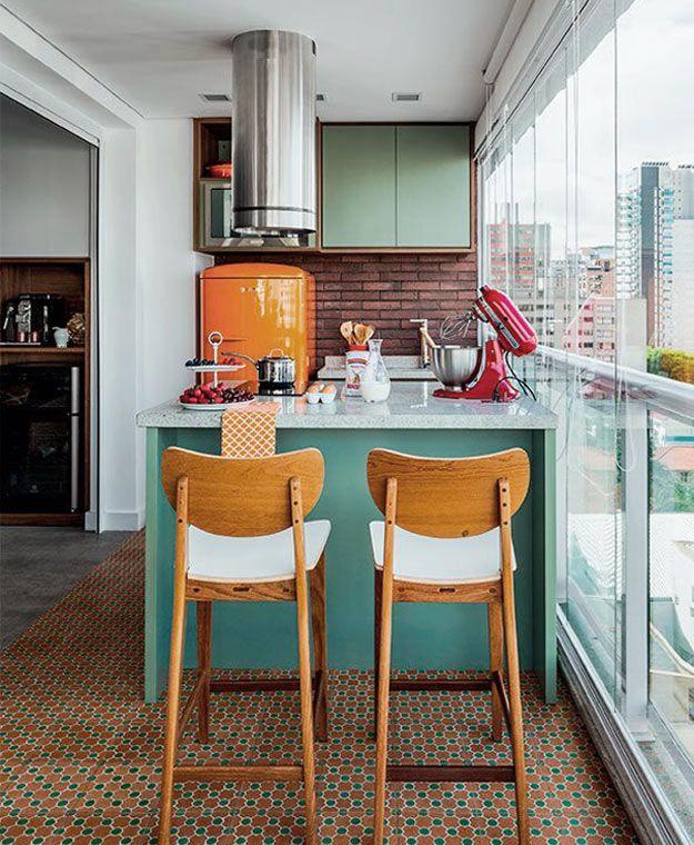 Colorida, este ambiente conta com dois tons de verde, na ilha e no armário, parede de tijolinhos e geladeira laranja.