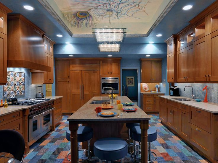 This eclectic blue kitchen design features a peacock feather mural on the ceiling above the kitchen island, blue tiled floor, wood cabinets, new appliances, retro blue stools, backsplash, and recessed lighting.