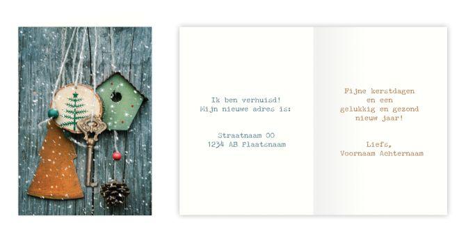 Op deze #kerstverhuiskaart hangt de sleutel (van het #nieuwehuis) tussen verschillende #kerstdecoraties tegen een houten achtergrond in de #sneeuw. - Sleutel kerst | Kerstverhuiskaart.nl