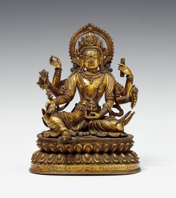 An exquisite Nepalese gilt bronze figure of Vasudhara. 18th century  An exquisite Nepalese gilt bronze figure of the six-armed Vasudhara, the goddess of fertility and wealth, seated at ease on a lotus base, holding in her hands a manuscript, an ear of grain, a treasure vase, a jewel, the rosary of the upper right hand lost, and the lower right hand in varada mudra. Incised with Tibetan script along the base. The sealed base cast separately. 18th century.  Height 18.3 cm