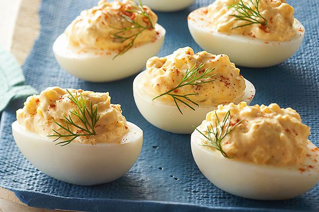 1 docena de huevos duros, cortados a lo largo por la mitad 3 cucharadas de crema agria  3 cucharadas de mayonesa  1 cucharada de condimento dulce de pepinillo Sweet Pickle Relish 1 cucharada de mostaza   1/8 cucharadita de pimienta roja (cayena) molida