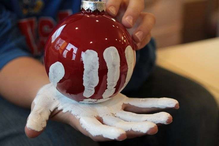 boule de Noël rouge décorée d'empreintes digitales de peinture blanche