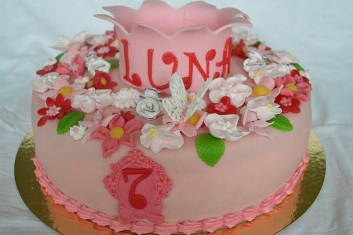 Flower cake. I love girly cakes. Deze taart is versiert met gespoten vlinders en bloemen van royal icing en bloemen van marsepein de kroon is van fondant met glitters. Gevuld met aardbeienjam en zwitserseroom.