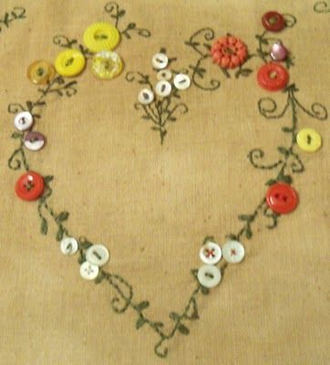 This has potential.  I would embroider the heart on the fabric, then make flower clusters with additional buttons.