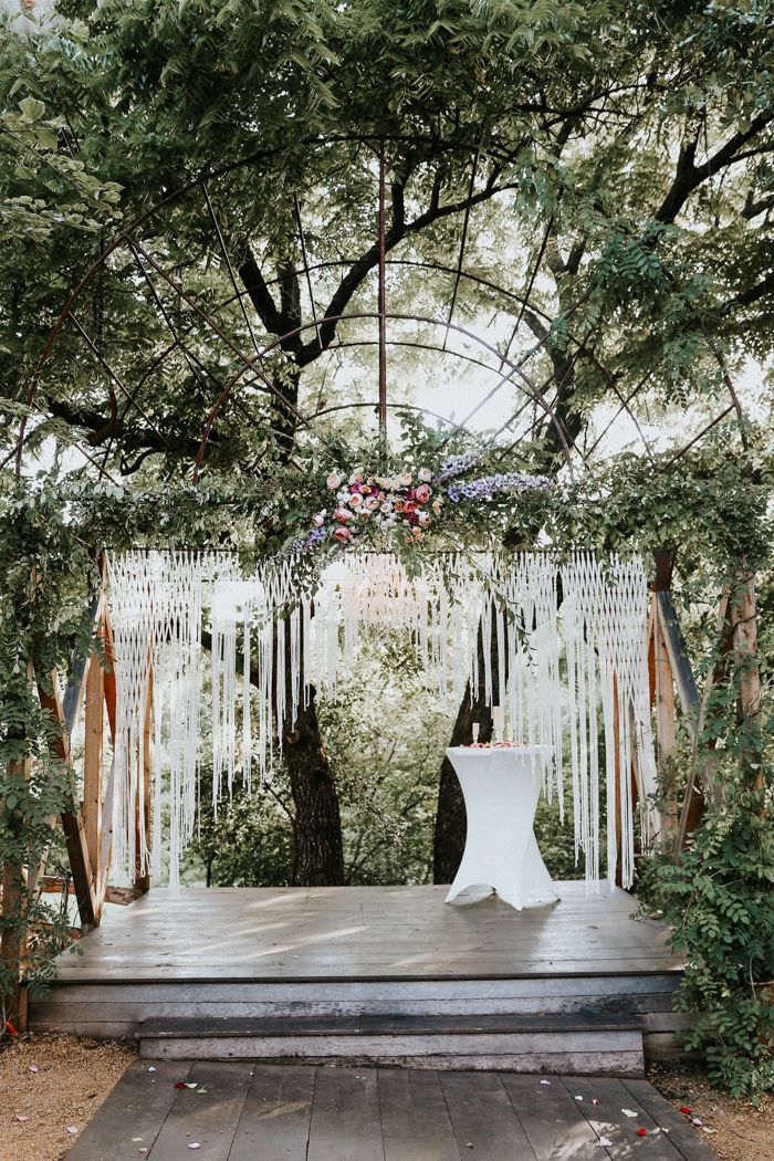 Macrame backdrop + overgrown floral design = bold/soft wedding decor style  | Image by  Melissa Marshall