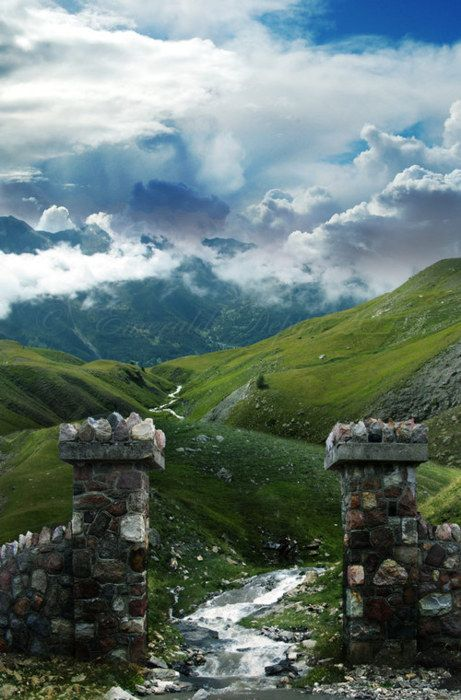 stone gate into a vast land of green fields and epic mountains and clouds