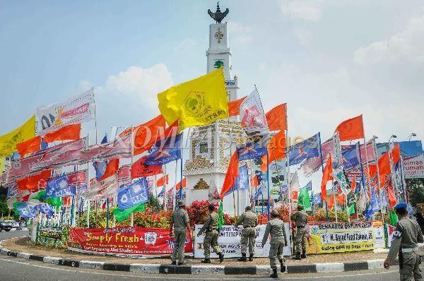 Petugas Satpol PP mencopot atribut kampanye calon anggota legislatif Pemilu 2014 di Bundaran Simpang Lima, Banda Aceh, Rabu (26/3/2014). Komisi Pemilihan Umum (KPU) telah mengatur ketentuan terkait pemasangan alat peraga kampanye luar ruangan dalam Peraturan KPU Nomor 15 Tahun 2013. Jalan utama menjadi salah satu zona yang bebas dari bendera partai politik
