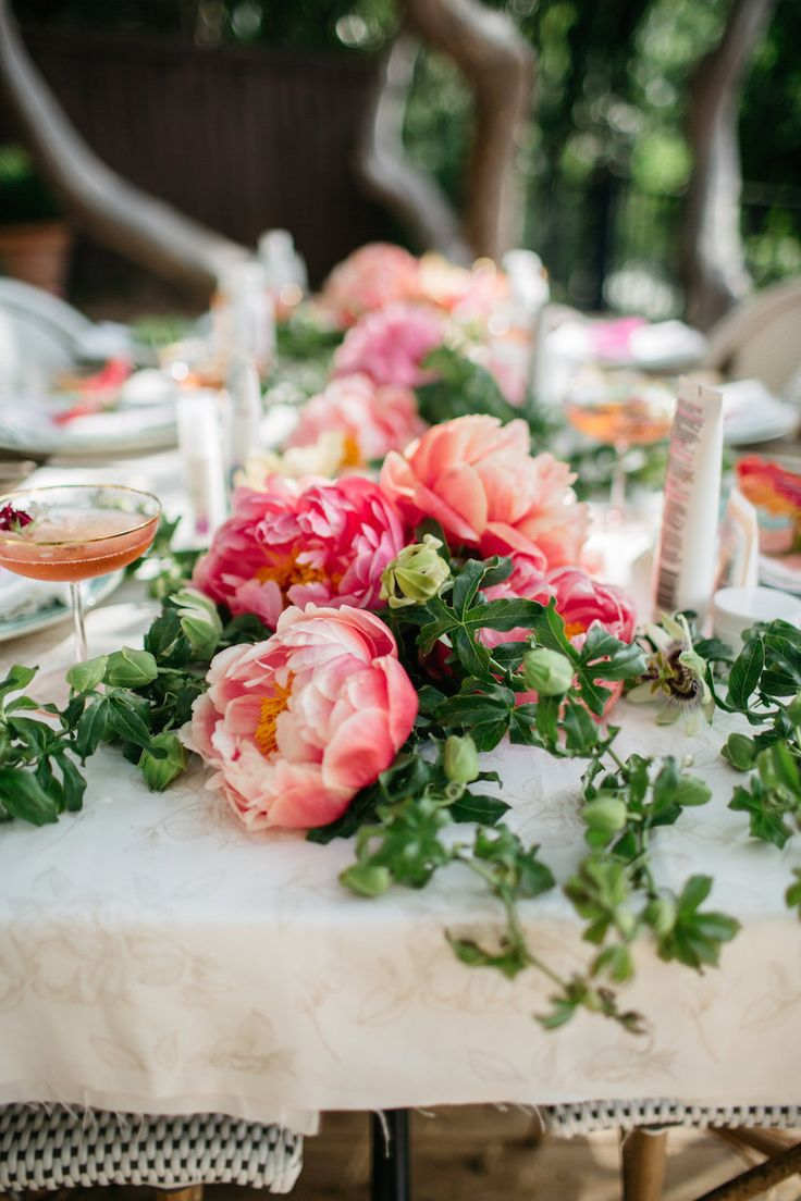 garden party table with coral charm peonies, passion vine, apricot parrot tulips, ranunculus, & juliette garden roses.
