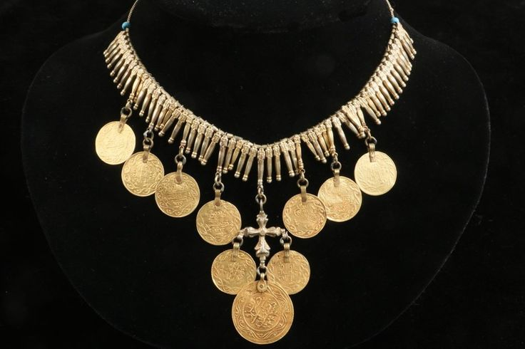 A delicate gold she'arieh necklace, probably from Hebron, Palestine, worn by a Christian Palestinian.  Or from the Ottoman empire. With gilt silver flower bud shapes and 10 golden coins from the period of Sultan Mahmud II (1836) and that of Sultan Abdulhamid II (1876.)